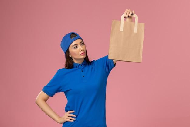Weiblicher kurier der vorderansicht im blauen uniformumhang, der papierlieferpaket auf hellrosa wand hält, service-mitarbeiterarbeit liefert