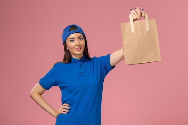 Weiblicher kurier der vorderansicht im blauen uniformumhang, der papierlieferpaket auf hellrosa wand hält, servicemitarbeiter, der arbeit liefert