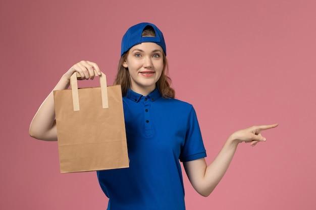 Weiblicher kurier der vorderansicht im blauen uniformumhang, der papierlieferpaket auf rosa wand hält, dienstlieferungsarbeitsangestellter