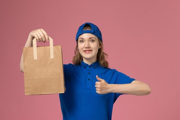 Weiblicher kurier der vorderansicht im blauen uniformumhang, der papierlieferpaket auf rosa wand hält, dienstlieferungsmitarbeiterarbeit
