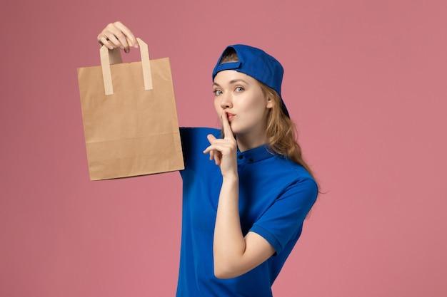 Weiblicher kurier der vorderansicht im blauen uniformumhang, der papierlieferpaket auf rosa wand hält, mitarbeiterdienstlieferarbeit