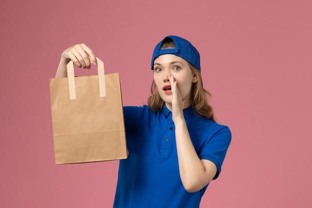 Weiblicher kurier der vorderansicht im blauen uniformumhang, der papierlieferpaket hält, das auf rosa wand flüstert, dienstlieferungsmitarbeiter