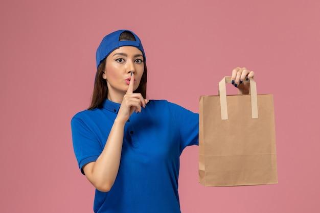 Weiblicher kurier der vorderansicht im blauen uniformumhang, der papierlieferpaket hält, das bittet, auf der hellrosa wand ruhig zu sein, servicemitarbeiter, das liefert