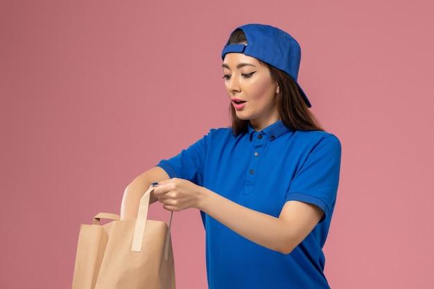 Weiblicher kurier der vorderansicht im blauen uniformumhang, der papierlieferpaket hält, das etwas auf der hellrosa wand herausnimmt, servicemitarbeiter, der arbeit liefert