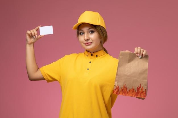Weiblicher kurier der vorderansicht im gelben einheitlichen gelben umhang, der lebensmittelpaket mit weißer karte auf dem rosa hintergrunduniformlieferarbeitsfarbjob hält