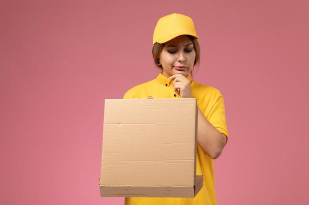Weiblicher kurier der vorderansicht im gelben einheitlichen gelben umhang, der lieferpaket auf der rosa hintergrunduniform-lieferauftragsarbeit hält