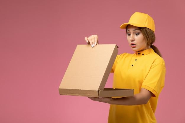 Weiblicher kurier der vorderansicht im gelben einheitlichen gelben umhang, der lieferpaket hält, das es auf dem rosa hintergrunduniformlieferauftrag öffnet