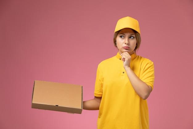 Weiblicher kurier der vorderansicht im gelben einheitlichen gelben umhang, der nahrungsmittelbox hält, der auf der weiblichen farbe der rosa schreibtischuniformlieferung denkt