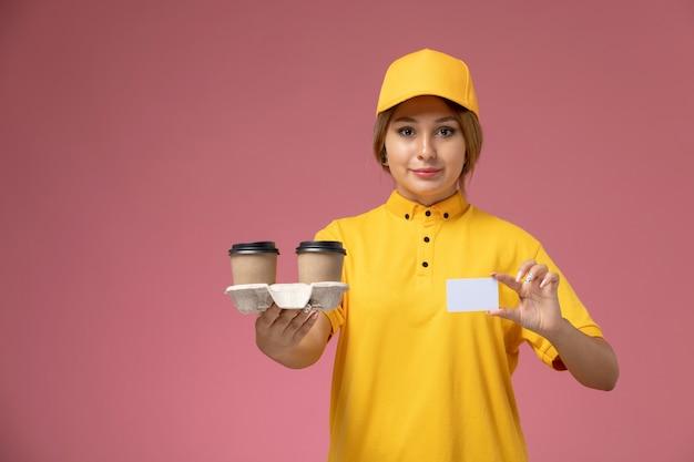 Weiblicher kurier der vorderansicht im gelben einheitlichen gelben umhang, der plastikweißkaffeetassen whtie karte auf der rosa schreibtischuniformlieferungsfrauenfarbe hält