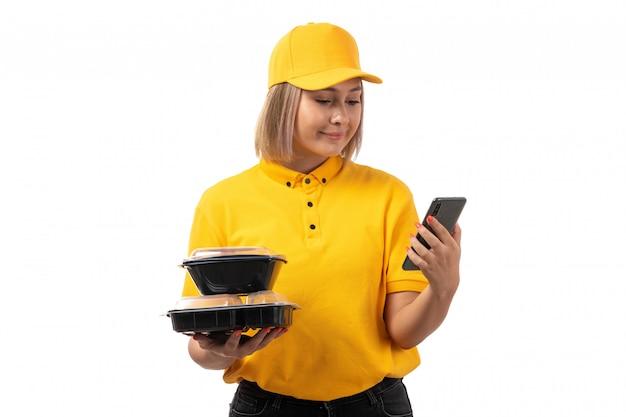 Weiblicher kurier der vorderansicht im gelben hemd und in der gelben kappe, die schüsseln mit essen und smarpthone halten, die auf weiß lächeln