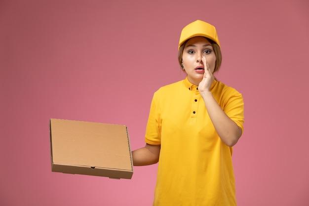 Weiblicher kurier der vorderansicht im gelben uniformgelbumhang, der nahrungsmittelbox hält und auf der weiblichen farbe der rosa schreibtischuniformlieferung flüstert