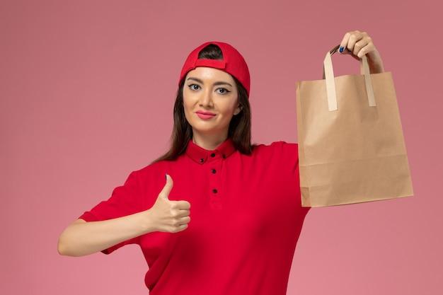 Weiblicher kurier der vorderansicht im roten uniformumhang mit lieferpapierpaket auf ihren händen auf rosa wand, arbeitsmädchen des einheitlichen lieferangestellten