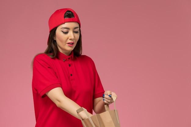 Weiblicher kurier der vorderansicht im roten uniformumhang mit lieferpapierpaket auf ihren händen auf rosa wand, arbeitsuniform-lieferangestellter