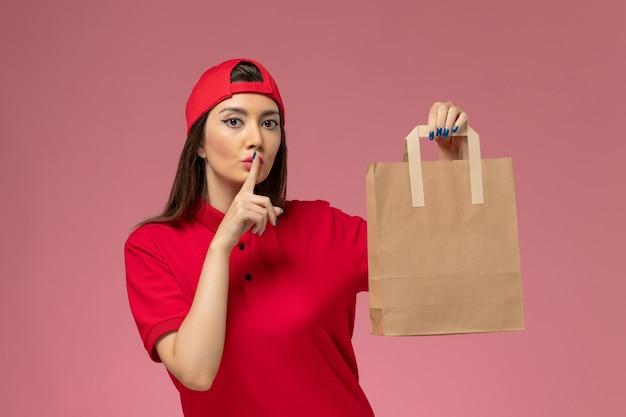 Weiblicher kurier der vorderansicht im roten uniformumhang mit lieferpapierpaket auf ihren händen, die bitten, auf rosa wand ruhig zu sein, uniformlieferungsangestellter