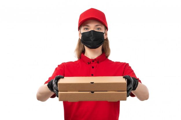 Weiblicher kurier der vorderansicht in den roten handschuhen der roten kappe der roten kappe und der schwarzen maske, die pizzaschachteln auf weiß hält