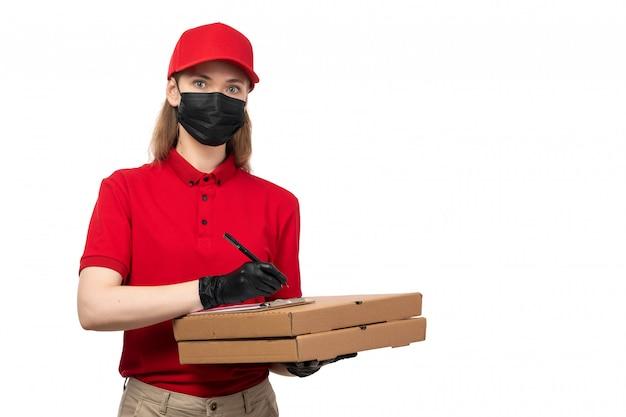 Weiblicher kurier der vorderansicht in den roten handschuhen der roten kappe der roten kappe und der schwarzen maske, die pizzaschachteln hält und befehle auf weiß schreibt