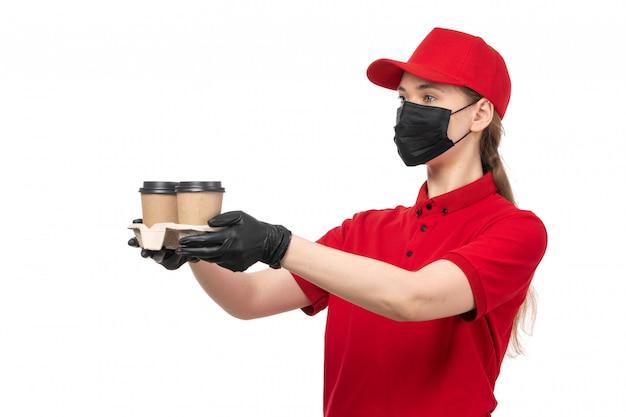 Weiblicher kurier der vorderansicht in den roten handschuhen der roten kappe des roten hemdes und der schwarzen maske, die kaffee hält