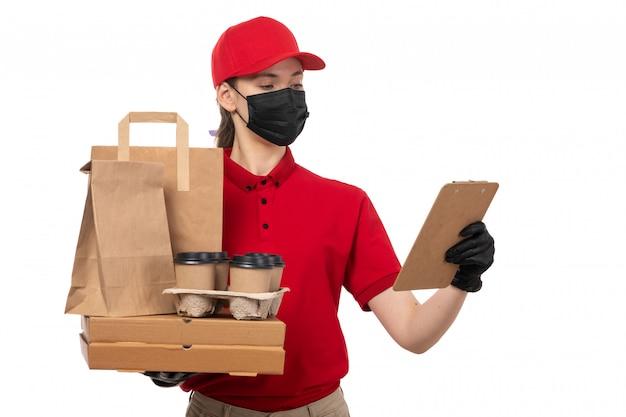 Weiblicher kurier der vorderansicht in den roten handschuhen der roten kappe des roten hemdes und der schwarzen maske, die lebensmittelverpackungen und kaffee auf weiß hält