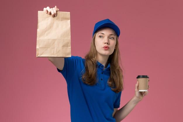 Weiblicher kurier der vorderansicht in der blauen uniform, die braune kaffeetasse mit lebensmittelpaket auf hellrosa hintergrunddienstuniform hält, die firma liefert