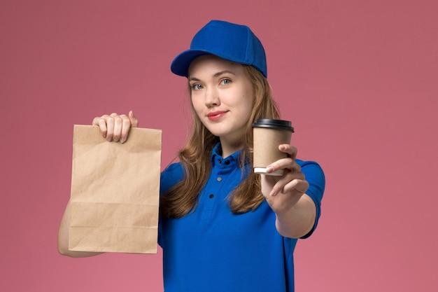Weiblicher kurier der vorderansicht in der blauen uniform, die braune kaffeetasse mit lebensmittelpaket und lächeln auf rosa schreibtischserviceuniform hält, die firma liefert