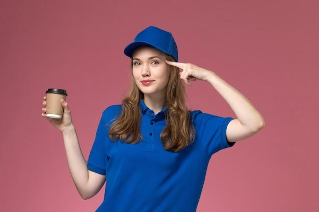 Weiblicher kurier der vorderansicht in der blauen uniform, die braune kaffeetasse mit leichtem lächeln auf hellrosa schreibtischdienstjobuniform-lieferfirma hält