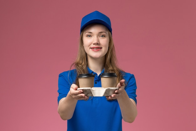 Weiblicher kurier der vorderansicht in der blauen uniform, die braune kaffeetassen auf rosa schreibtischdienstuniform liefert, die firmenjob liefert