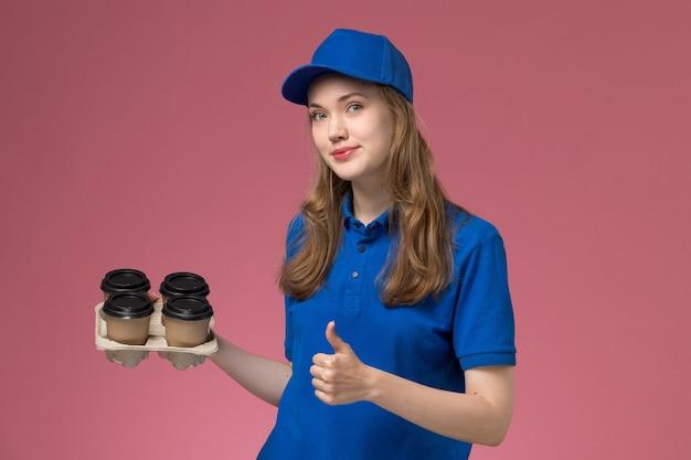 Weiblicher kurier der vorderansicht in der blauen uniform, die braune kaffeetassen der lieferung hält, die wie zeichen auf rosa schreibtischdienstuniformfirmaarbeiter zeigen