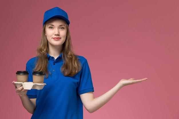 Weiblicher kurier der vorderansicht in der blauen uniform, die braune kaffeetassen mit leichtem lächeln auf der rosa hintergrunddienstuniform hält, die firmenjob liefert