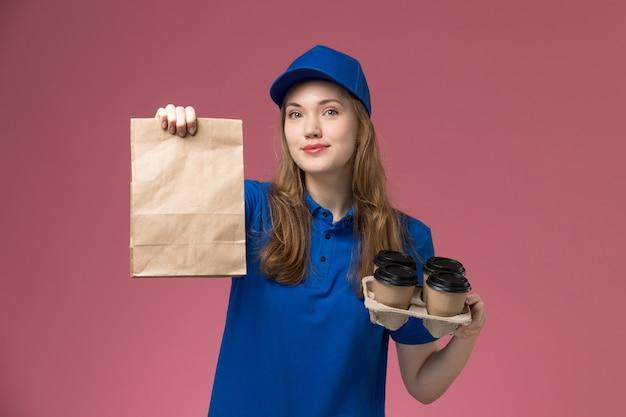 Weiblicher kurier der vorderansicht in der blauen uniform, die braune lieferkaffeetassen mit lebensmittelpaket auf rosa schreibtischdienstuniform-firmenarbeiter hält