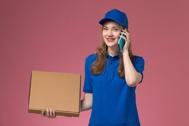 Weiblicher kurier der vorderansicht in der blauen uniform, die lebensmittel-lieferbox hält und am telefon auf rosa schreibtischdienstuniform-firmenjob spricht