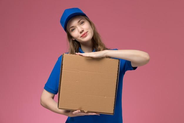 Weiblicher kurier der vorderansicht in der blauen uniform, die lebensmittelbox mit lächeln auf rosa schreibtischjobdienstuniformfirma hält