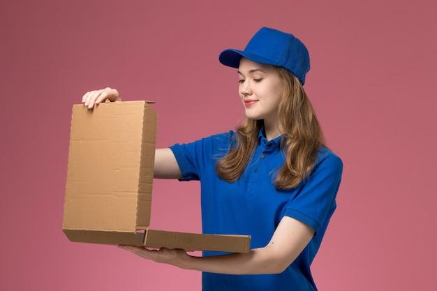 Weiblicher kurier der vorderansicht in der blauen uniform, die nahrungsmittelbox offen hält, öffnen sie auf rosa hintergrundjobarbeiterdienstuniformfirma