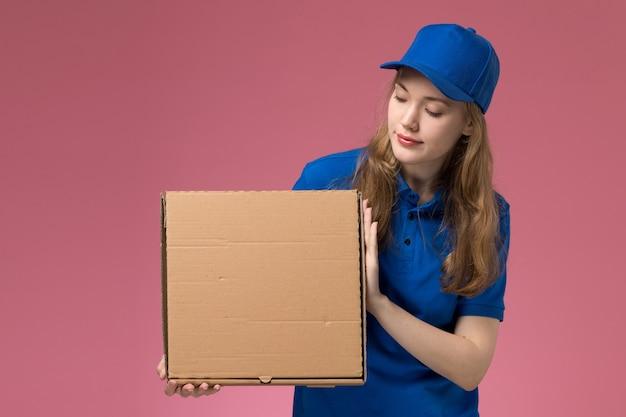 Weiblicher kurier der vorderansicht in der blauen uniform, die nahrungsmittellieferbox auf der rosa hintergrundjobdienstuniformfirma hält