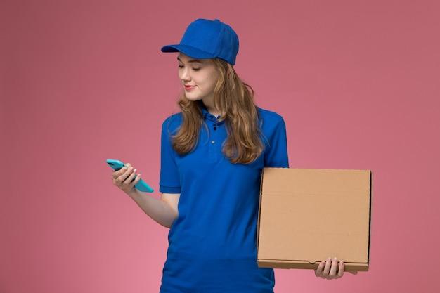Weiblicher kurier der vorderansicht in der blauen uniform, die nahrungsmittellieferbox und -telefon auf dem firmenjob der rosa schreibtischarbeiterserviceuniform hält