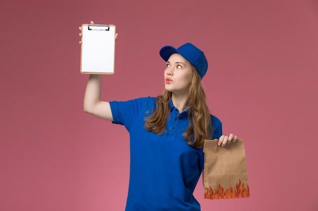 Weiblicher kurier der vorderansicht in der blauen uniform, die notizblock und nahrungsmittelpaket auf der rosa schreibtischjobarbeitsdienstuniformfirma hält