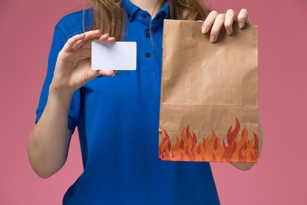 Weiblicher kurier der vorderansicht in der blauen uniform, die weiße karte und lebensmittelpaket auf rosa hellem schreibtischdienstuniformfirmenjob hält