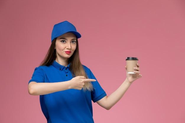Weiblicher kurier der vorderansicht in der blauen uniform und im umhang, der die kaffeetasse der lieferung auf der rosa wandmädchenarbeitsarbeit hält