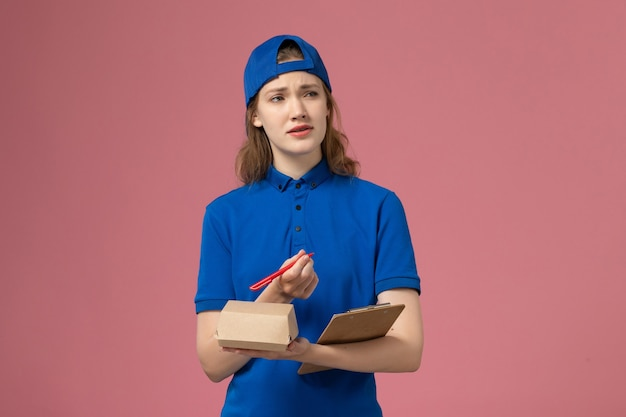 Weiblicher kurier der vorderansicht in der blauen uniform und im umhang, der kleinen notizblock des zustellungsnahrungsmittelpakets hält und auf die rosa wand schreibt, lieferservice-mitarbeiterarbeit