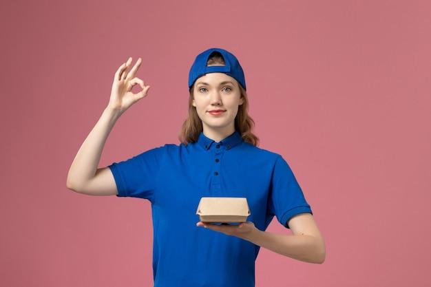Weiblicher kurier der vorderansicht in der blauen uniform und im umhang, der kleines liefernahrungsmittelpaket auf dem rosa hintergrundlieferuniform-dienstleistungsmädchen hält
