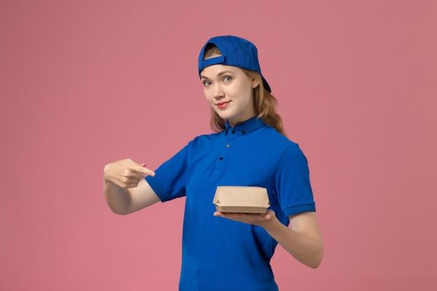 Weiblicher kurier der vorderansicht in der blauen uniform und im umhang, der kleines liefernahrungsmittelpaket auf dem rosa hintergrundlieferuniformuniversitätsarbeitsarbeitsarbeiter hält