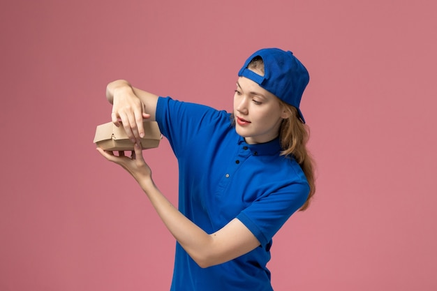 Weiblicher kurier der vorderansicht in der blauen uniform und im umhang, der kleines liefernahrungsmittelpaket hält und es auf der rosa wand, lieferuniform-servicefirma öffnet
