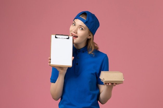 Weiblicher kurier der vorderansicht in der blauen uniform und im umhang, der kleines liefernahrungsmittelpaket und notizblock auf rosa wand, lieferservice-mitarbeiter hält