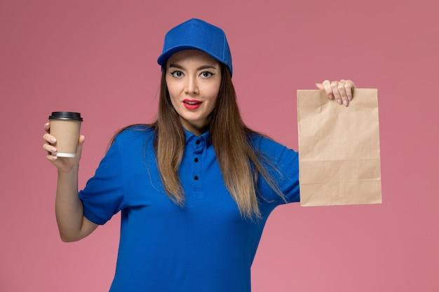Weiblicher kurier der vorderansicht in der blauen uniform und im umhang, der lieferung kaffeetasse-lebensmittelpaket an der rosa wand hält
