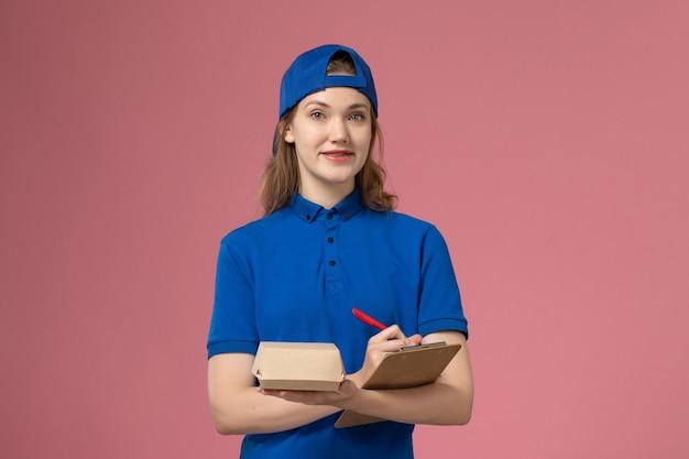 Weiblicher kurier der vorderansicht in der blauen uniform und im umhang, der notizblock des kleinen liefernahrungsmittelpakets hält und auf die rosa wand schreibt, lieferservice-mitarbeiterjob