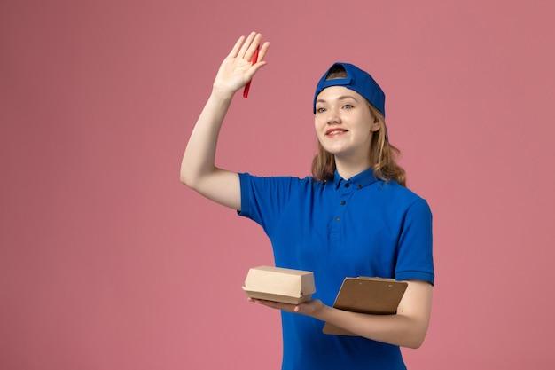 Weiblicher kurier der vorderansicht in der blauen uniform und im umhang, der notizblock des kleinen liefernahrungsmittelpakets hält und auf rosa wand schreibt, joblieferdienstmitarbeiterarbeit