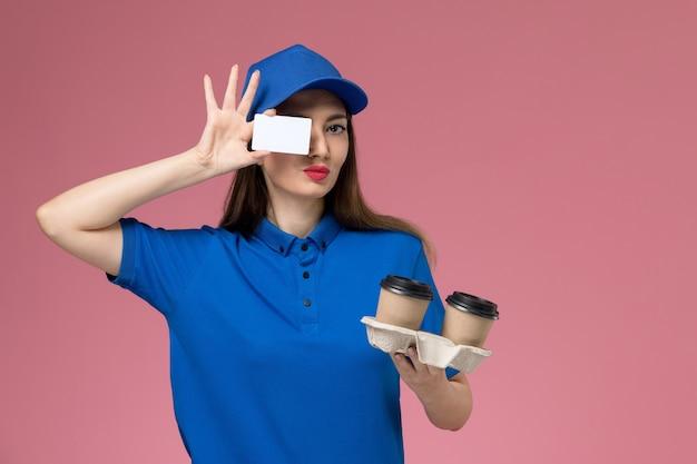 Weiblicher kurier der vorderansicht in der blauen uniform und im umhang, die braune kaffeetassen und karte der lieferung auf rosa wandfrau halten