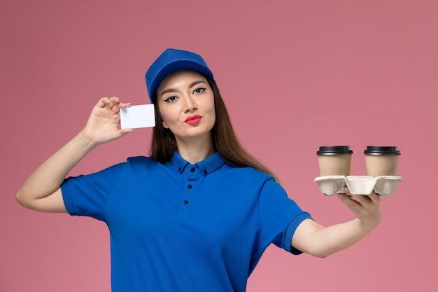 Weiblicher kurier der vorderansicht in der blauen uniform und im umhang, die braune kaffeetassen und karte der lieferung halten, die auf rosa wand aufwerfen