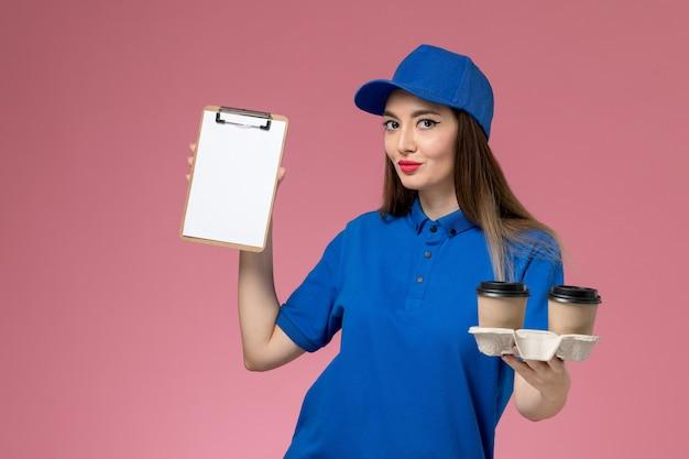 Weiblicher kurier der vorderansicht in der blauen uniform und im umhang, die braune kaffeetassen und notizblock halten, die auf rosa wand lächeln