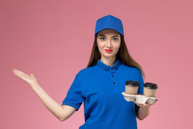 Weiblicher kurier der vorderansicht in der blauen uniform und im umhang, die kaffeetassen der lieferung an der rosa wand halten