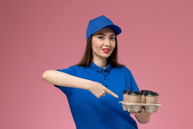 Weiblicher kurier der vorderansicht in der blauen uniform und im umhang, die kaffeetassen der lieferung halten, die auf hellrosa wand lächeln